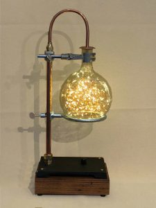 Handmade copper, American Chestnut and glass lamp features a copper gooseneck and clear globe filled with tiny led string light leds.