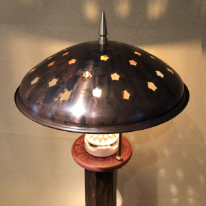 soft lighted star shapes shine through the hand spun copper dome shade of this desk lamp.