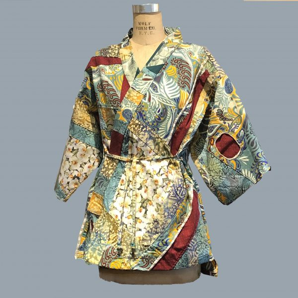 white orchids anchor the more varied African print textile in this short coat with red accents.